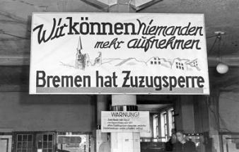 Rechts oben: Zuzugssperre für Bremen, 1946. Diese Tafel wurde am 2. Juli 1945 vom Flüchtlingsamt am Hauptbahnhof in Bremen aufgehängt, da die Stadt zu sechzig Prozent in Trümmern lag. © Staatsarchiv Bremen / Foto: Karl Edmund Schmidt