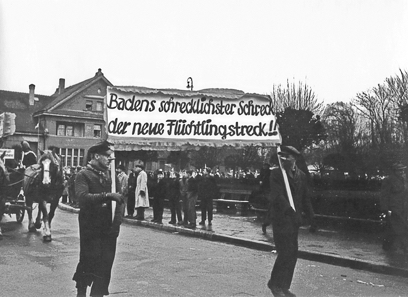 """Fastnachtsumzug im badischen Lahr, Ende der 1940er Jahre. Verkleidete Männer tragen ein Plakat mit einer Parole gegen Flüchtlinge: """"Badens schrecklichster Schreck, der neue Flüchtlingstreck!!!"""" © Stadtarchiv Offenburg"""